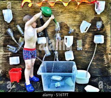 Jeune garçon se renverser de l'eau dans une bouteille sur le mur d'eau Banque D'Images