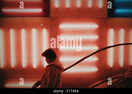 Woman riding un escalator en face de néons rouge Banque D'Images