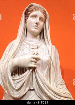 Statue en marbre classique d'une jeune fille romaine avec fond orange. Banque D'Images