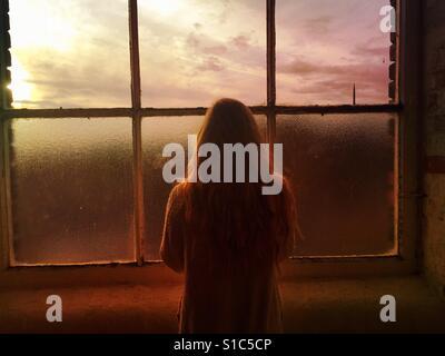 Vue arrière d'une femme seule en regardant par la fenêtre au coucher du soleil Banque D'Images
