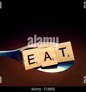 Close up d'une cuillère en bois avec lettres sur elle l'orthographe du mot manger Banque D'Images