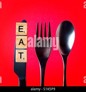 Un gros coup de frais généraux d'un couteau et une fourchette et une cuillère au-dessus d'un fond rouge avec le Banque D'Images