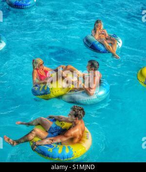 Vacances d'été - assis et couché à l'intérieur de bagues en plastique gonflables et vous détendre dans une piscine Banque D'Images