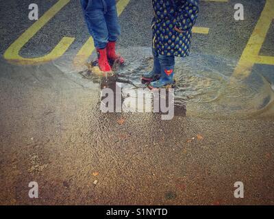 Deux enfants dans des bottes de pluie qui saute dans une flaque Banque D'Images