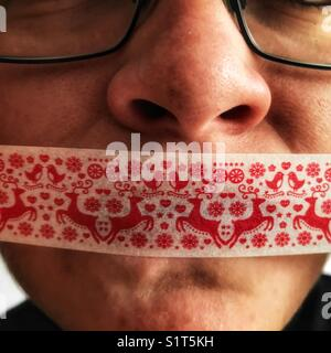 Young woman's face with christmas gift tape sur sa bouche Banque D'Images