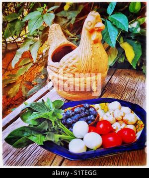 Un bol est rempli d'épinards frais, œufs, tomates, champignons, bleuets et gigantesque sur une table rustique avec Banque D'Images