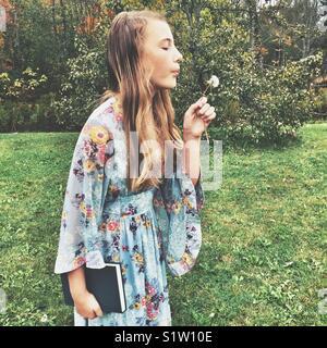 Girl vintage 60's era dress blowing sur blanches à l'extérieur de pissenlit Banque D'Images