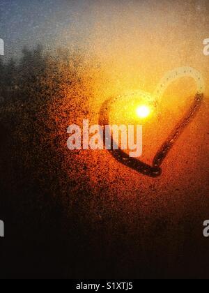 Lever du soleil à travers le brouillard de l'eau sur la fenêtre avec cœur dessiné autour de soleil Banque D'Images