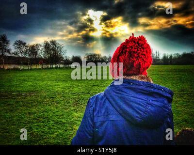 Dame avec un manteau bleu et rouge, en bobble hat à marcher vers le soleil du matin dans un parc à Warrington Banque D'Images