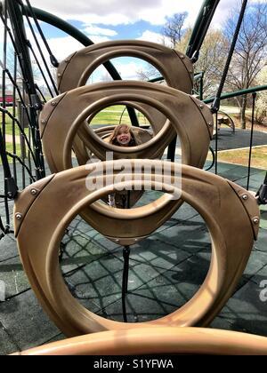 Une petite fille monte à l'équipement de jeu à Bentonville, Arkansas. Banque D'Images