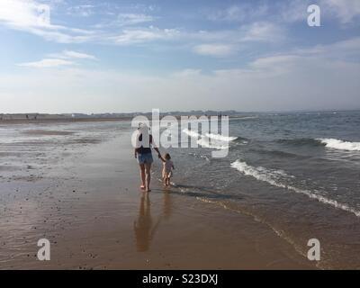 Mère et fille marcher sur la plage un jour d'été Banque D'Images