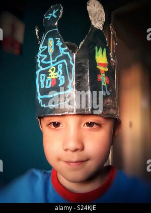 Portrait d'un jeune garçon portant une couronne faite maison. Banque D'Images