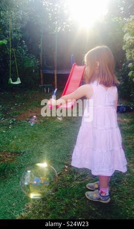 Petite fille faisant des bulles dans le jardin avec un faible soleil du soir. Banque D'Images