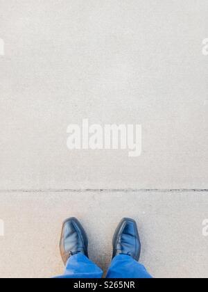 Point de vue personnel d'un homme debout en face d'une ligne tracée sur le sol. Banque D'Images