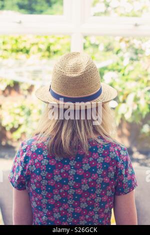 Vue arrière d'une jeune fille dans une jolie robe et chapeau de paille Banque D'Images