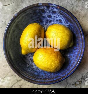 Trois citrons frais dans un bol en céramique bleu Banque D'Images