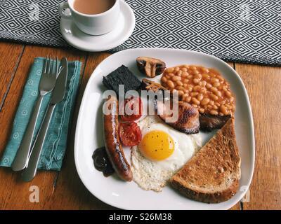 Un petit-déjeuner anglais complet fait maison, avec des saucisses, des tomates, du boudin noir, champignons, haricots blancs, pain grillé, sauce brune, un œuf frit, et une tasse de thé. Banque D'Images