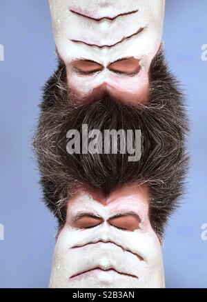 Une image abstraite d'une femme portant un masque de boue blanche aux yeux clos et plusieurs bouches et les cheveux foncés dupliqué pour créer un étrange alien Banque D'Images