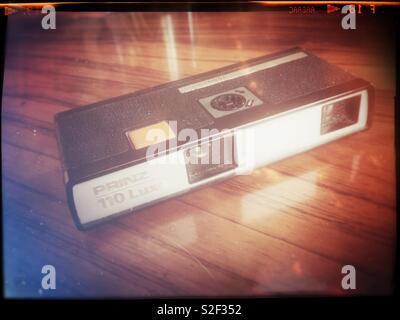 Un appareil photo de poche vintage ca 1972 en configuration redondante 110 film format sur une table en acajou. Traitement rétro. Banque D'Images