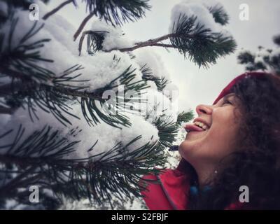 Happy young woman eating et profiter de l'hiver la neige d'un pin de montagne