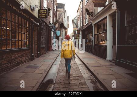 Une vue arrière d'un jeune fille qui marche le long d'une rue médiévale historique connue comme la pagaille dans la ville historique de York, Royaume-Uni Banque D'Images