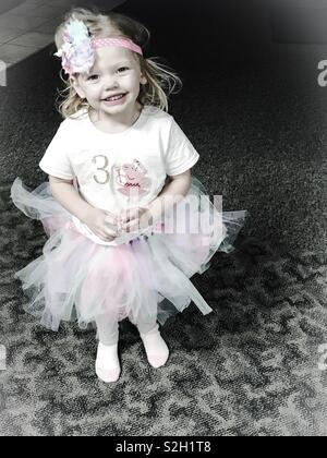 Petite fille portant un bandeau et un Peppa Pig T-shirt avec le numéro 3 sur elle pour son âge à son anniversaire Banque D'Images