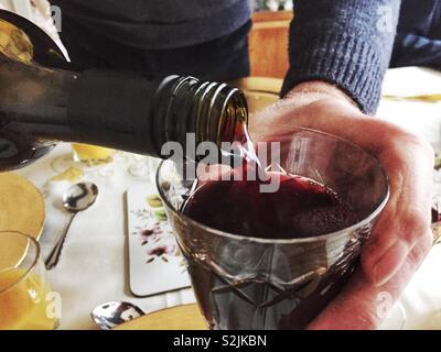Un homme se verse un verre de vin rouge. Banque D'Images