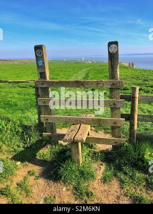 Stile sur le chemin côtier du Glamorgan avec Nash Point Lighthouse dans la distance. Banque D'Images