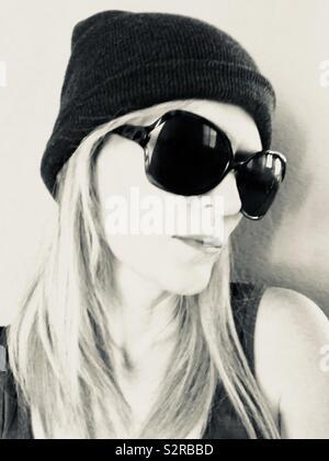 Une image monochrome noir et blanc d'une belle jeune fille aux cheveux blonds portant un Beanie Hat avec des lunettes