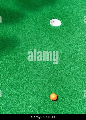 Mini Putt-putt golf balle de golf orange miniature sur vert loin de tasse Banque D'Images