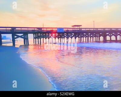 Lever de soleil derrière une jetée à Myrtle Beach en Caroline du Sud. Les gens se trouvent à l'extérieur sur la plage. Banque D'Images