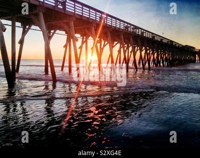 Lever du soleil derrière une jetée à Myrtle Beach en Caroline du Sud. Les reflets lumineux du soleil levant crée un intérêt visuel. Banque D'Images