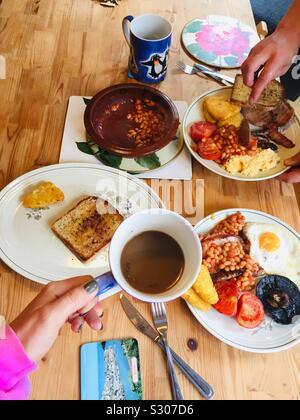 Le petit déjeuner anglais complet sur la table de la cuisine. Frits dans l'huile d'olive pain, champignons, pommes de terre rissolées, les haricots, oeufs, tomates, saucisses, œufs brouillés, café et thé.Un petit-déjeuner fait maison pour deux. Londres Banque D'Images