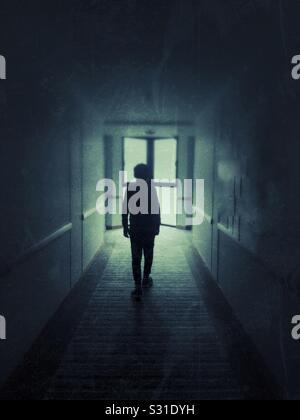 Silhouette de garçon, promenade dans un couloir de chambre d'hôtel Banque D'Images