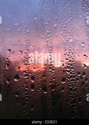 Condensation (gouttelettes d'eau) sur une fenêtre en gros plan, avec une aube rose et violette dans le ciel vu à travers elle. Banque D'Images