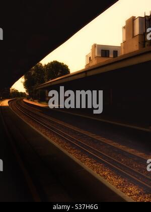 Les voies ferrées coupent le spectateur avant de s'éloigner à l'infini. Une lumière chaude et radiante s'installe sur une scène qui est largement dans l'ombre profonde. Les plates-formes de station sont visibles dans l'ombre. Banque D'Images