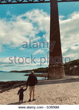Grand-père et petit-fils tenant les mains marchant le long de la plage ensoleillée pendant l'été