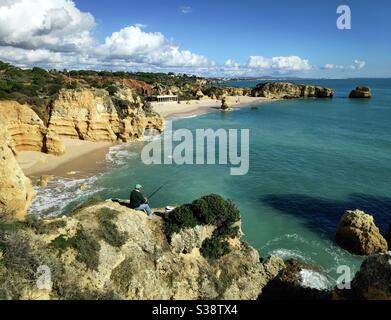 Un pêcheur à la plage de Praia de São Rafael en Algarve, Portugal Banque D'Images