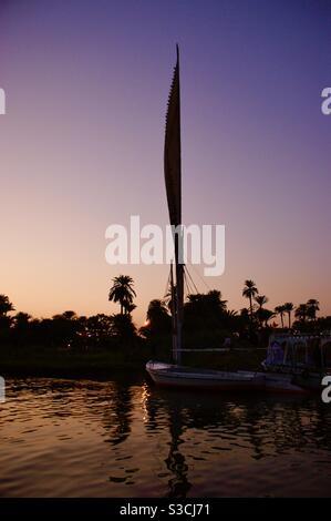 Magnifique et élégant felucca bateau traditionnel naviguant sur le Nil au coucher du soleil près de Louxor, Egypte