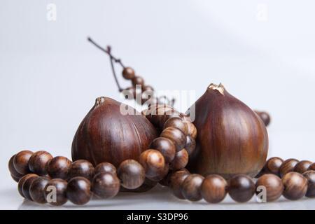 De délicieux châtaignes mûres bio, enveloppées de près dans des perles de prière isolé sur fond blanc