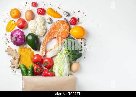 Supermarché. Sac de papier plein d'aliments sains sur un fond blanc. Vue d'en haut. Mise à plat. Copier l'espace. Banque D'Images