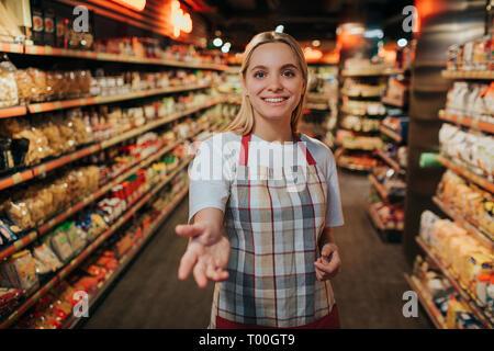 Jeune femme attendre en ligne entre deux tablettes de pâtes en épicerie. Elle part rejoindre à l'appareil photo et de sourire. Model posing. Banque D'Images