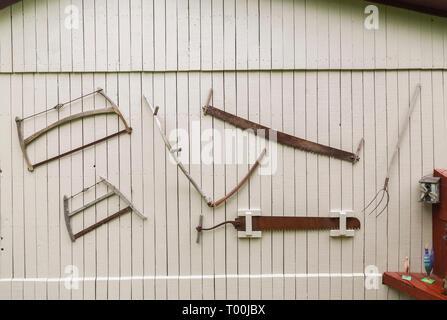 Scies antique, pitchfork et autres outils à main accroché sur le mur de côté de l'ancienne grange en bois peint en gris recouvert en arrière-cour résidentielle Banque D'Images