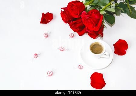 Tasse de café noir avec un bouquet de roses rouges sur fond clair Banque D'Images