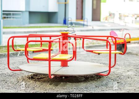 Carrousel rouge sur l'aire de jeux dans la ville. La notion d'enfance, parentalité, jeu