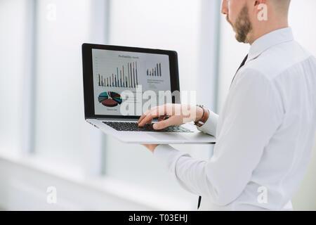Close up. businessman analyser les données financières sur l'ordinateur portable Banque D'Images