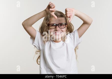 Petite fille montre le mauvais signe du pouce, l'aversion, négatif. Sur fond blanc en blanc T-shirt de base. Banque D'Images