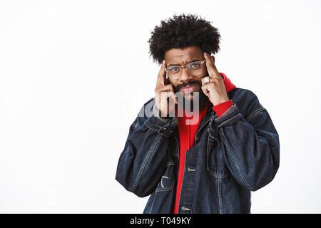 Portrait de confus et triste frustated african american man ne peut pas avoir des maux de tête ou migraine holding doigts sur les temples de froncer et grimaces Banque D'Images