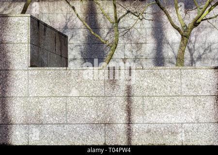 Vue urbaine avec un mur bordé de dalles de pierre de marbre et arbres en arrière-plan. Banque D'Images