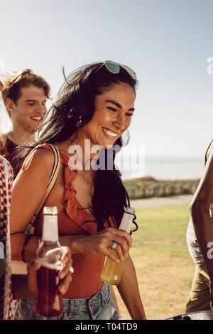 Belle femme avec de la bière la marche à l'extérieur avec des amis. Amis marchant avec des boissons sur une journée d'été. Banque D'Images